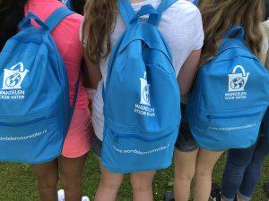 Kinderen met rugzakjes voor de sponsorloop wandelen voor water